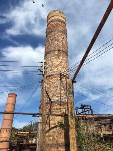 A brick chimney towers over a nearby kiln at a defunct clay plant.