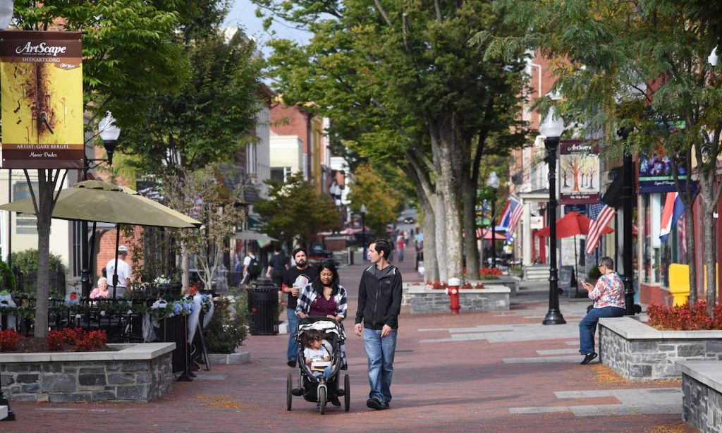 a young family with others pictured around the frame are walking through a downtown street with small shops and trees in planters