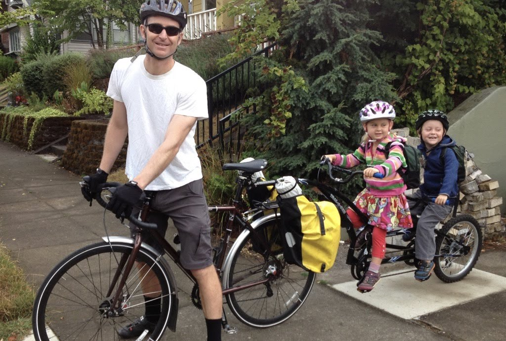 Chris Rall and his two twins pictured on a bike.