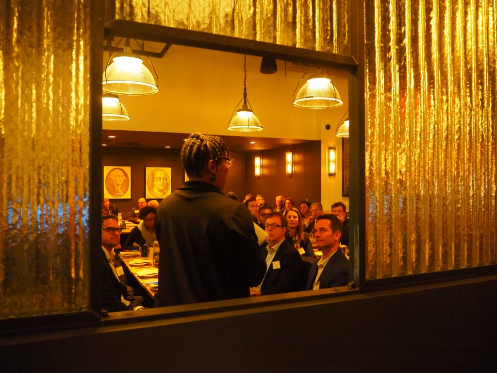 Visible through an opening in the wall, Anita Cozart delivers remarks at the 10th Annual Complete Streets dinner.