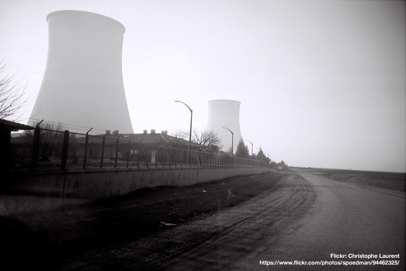 black and white photo of a nuclear power plant with cooling towers shrouded in mist