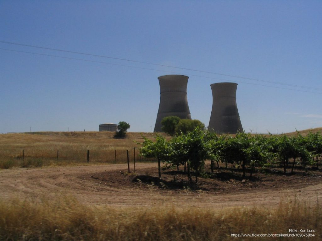 Photo of the cooling towers of a decommissioned nuclear plant rising above fields of crops