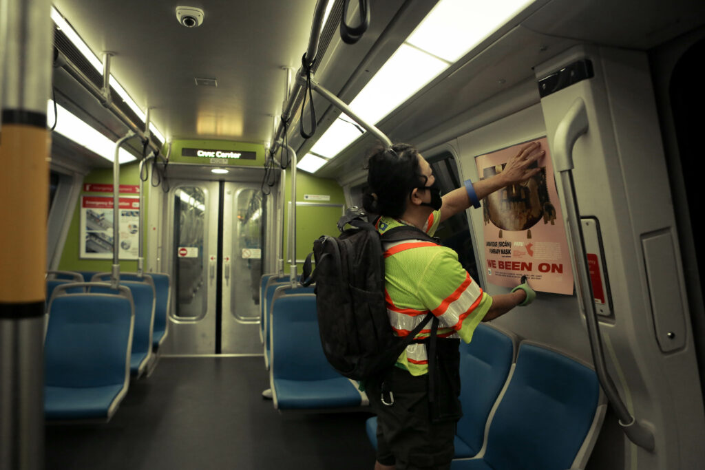 Image of person installing a pink poster featuring an image of a wooden cultural mask onto the side of a train car.