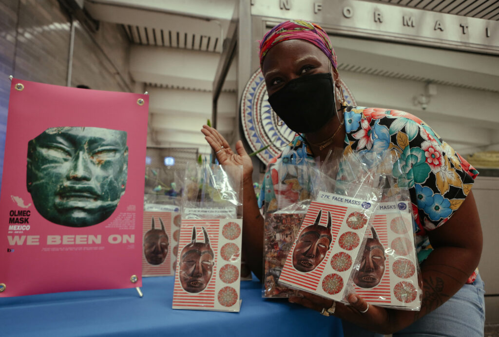 "Image of person crouching next to a pink poster that reads ""We been on"" and features a slate colored cultural mask. Person holds in their hands a number of clear giveaway bags containing art postcards."