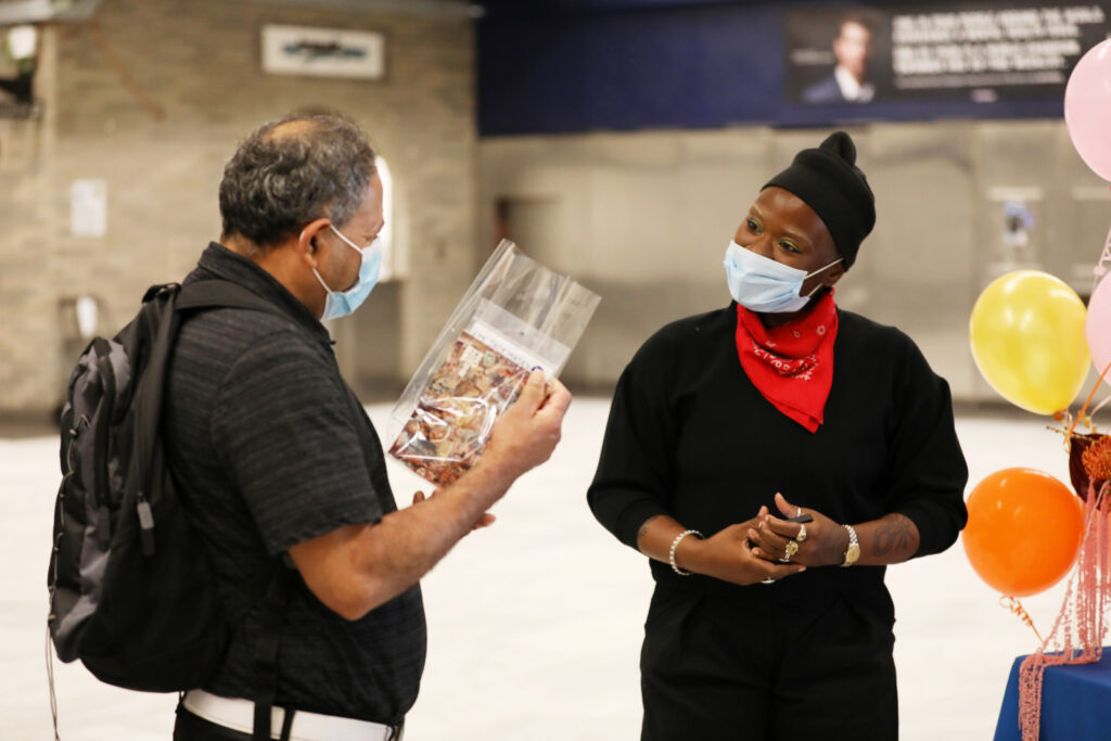 Image of two people wearing masks talking inside a transit station. Person on the left holds in their hand a clear plastic bag with a pink postcard inside.