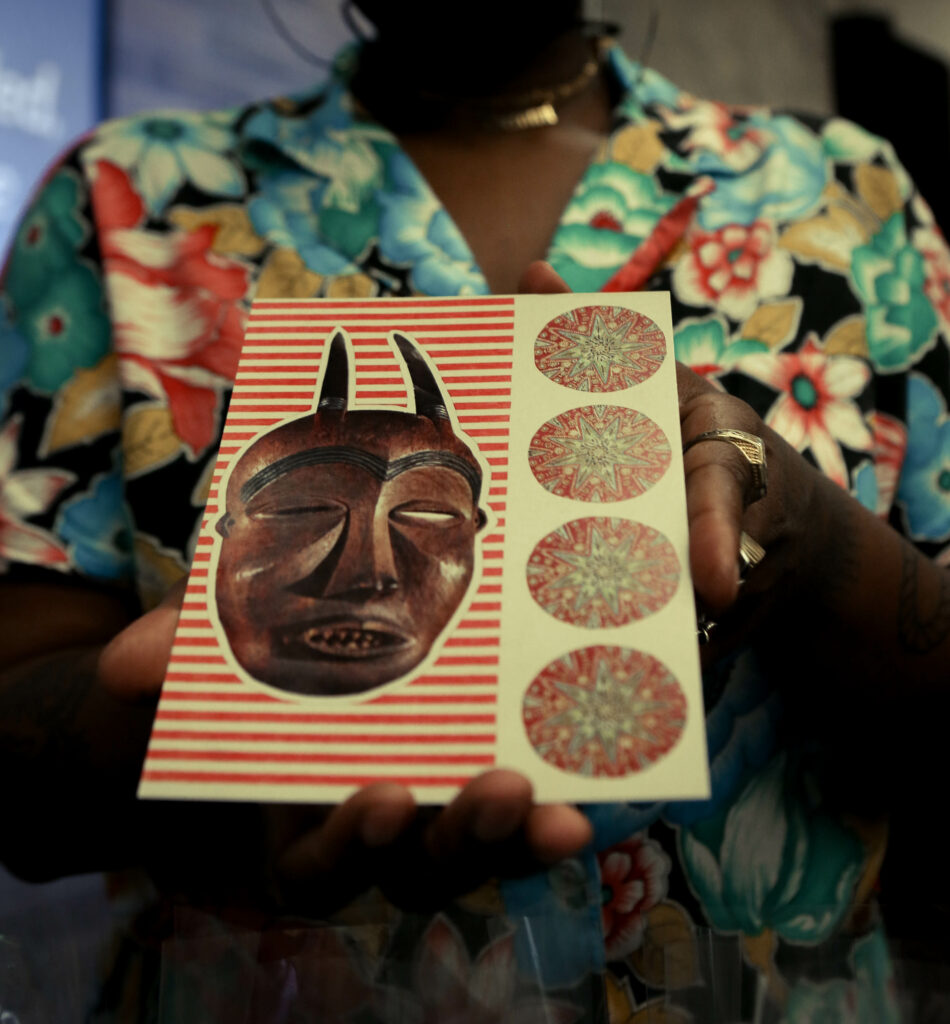Image of a person holding a postcard with a red wooden cultural mask.