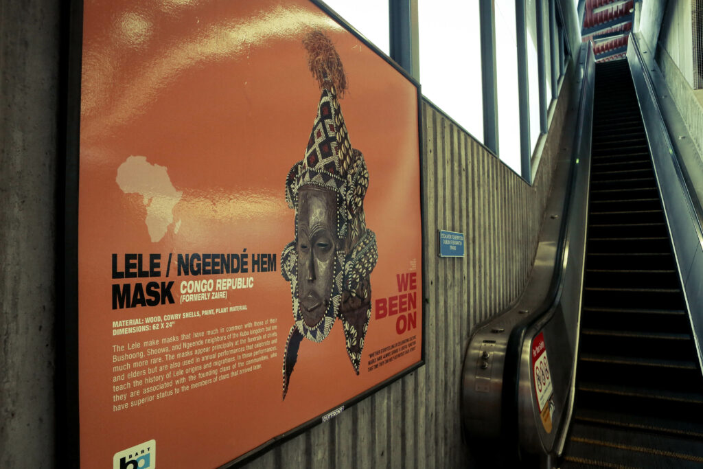 Image of a orange poster featuring a wooden mask from Congo Republic in front of an escalator in a transit station.
