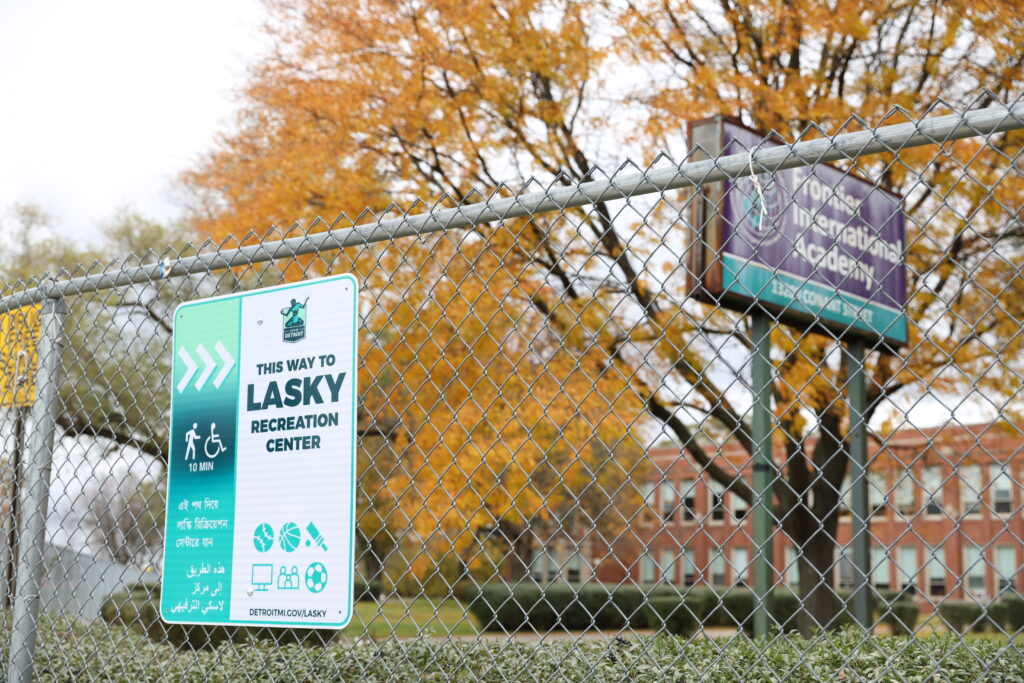 Image of teal and white sign attached to fence that features the Detroit logo and directs people to Lasky Recreation Center.