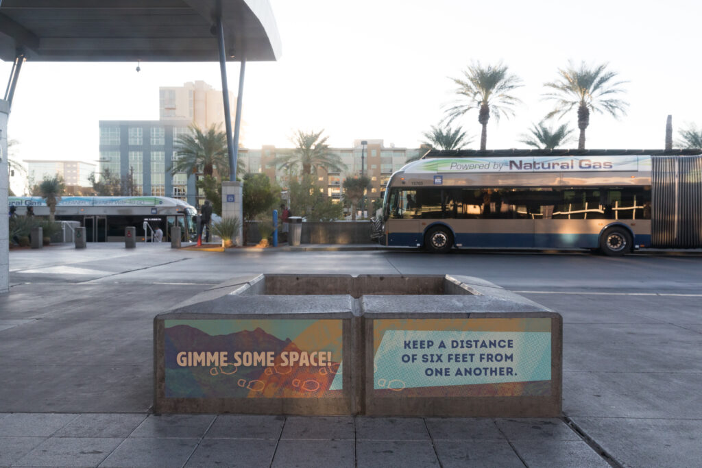 """Image of two vinyl signs adhered to a concrete seating area which read """"Gimme some space!"""" and """"Keep a distance of 6 feet from one another."""" In the background are buses and palm trees."""