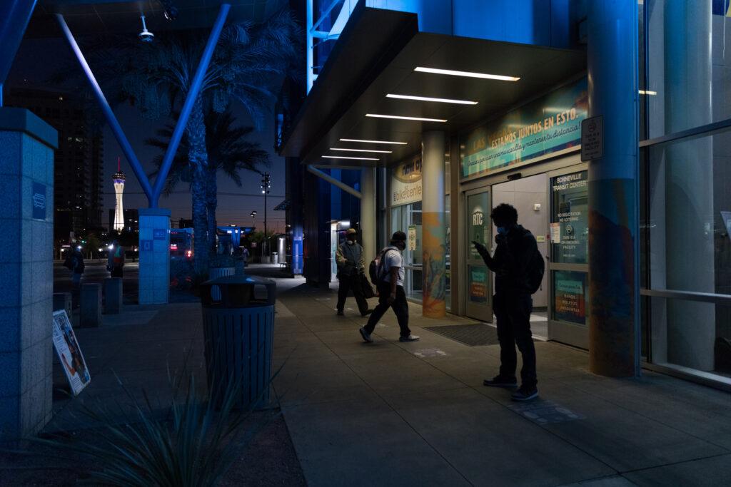"Image of the entrance of Bonneville Transit Center at night featuring vinyl signs on glass doors that read ""Estamos juntos en esto."""