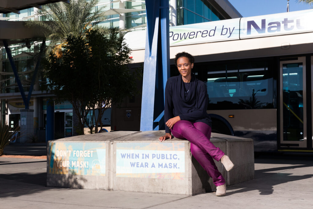 """Image of a person sitting on a concrete seating area. Attached to the concrete seating area is signage that reads """"DON'T FORGET YOUR MASK!"""" and """"When in public, wear a mask."""""""