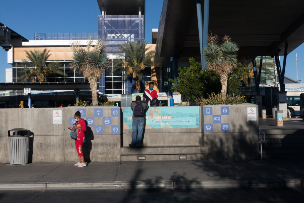 """Image of people gathering at a seating area outside of Bonneville Transit Center. Vinyl signage in the seating area includes small blue icons with symbols of buses, people, and footprints and a larger sign that reads """"Dude, where is your mask?"""" and below in smaller font """"Masks keep you and others safe."""""""
