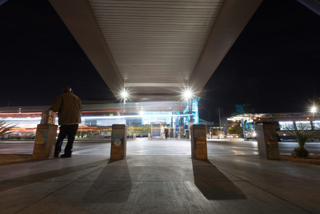 Image of Bonneville Transit Center at nightime. Vertical columns display messaging telling people to stay two arms apart.