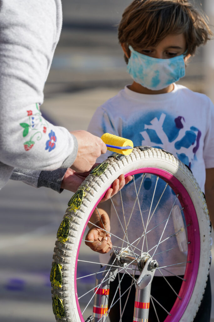 Image of young person watching as an adult applies yellow paint to the footprints attached to the wheel of the play sculpture.