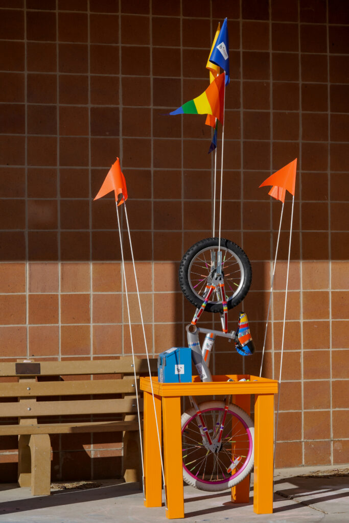 Image of orange bike sculptural table featuring bicycle parts, wheels, and multi-colored flags.
