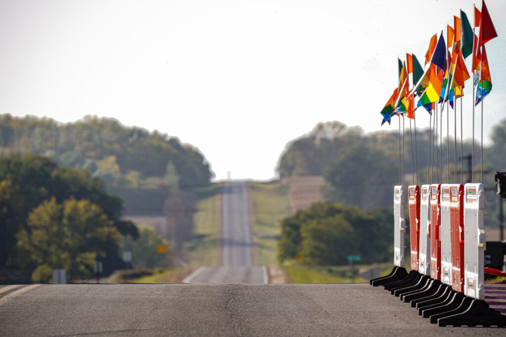 Image of empty rural highway and barricades on the right side that are topped with rainbow flags.