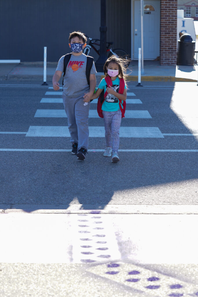Image of two young people walking on a crosswalk towards a set of stenciled purple footprints on the sidewalk.