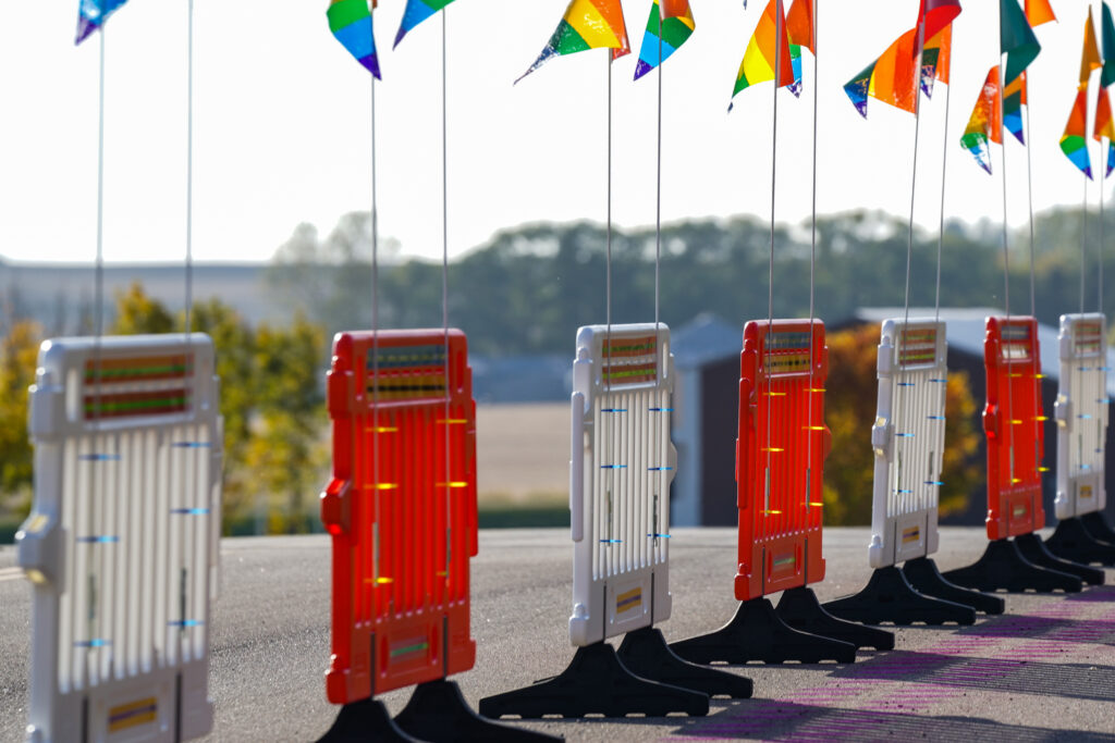 Image of series of orange and white barricades topped with rainbow flags.