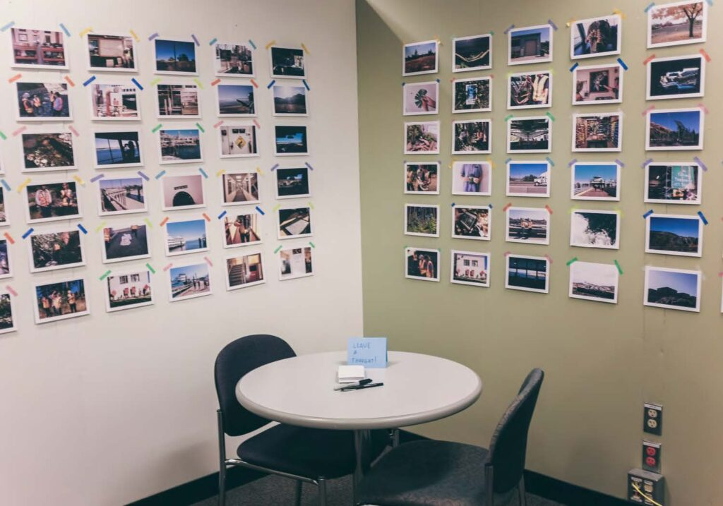 Image of the corner of a room with numerous photos taped to the walls. In the foreground is a table with two chairs.