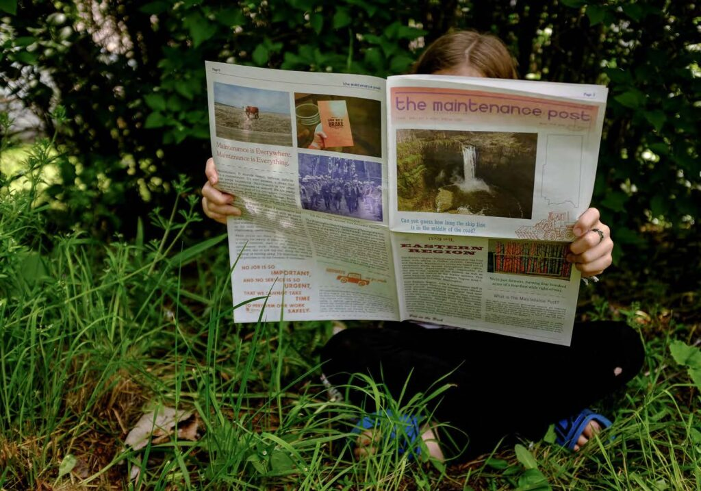 Image of person sitting on the grass and holding up a newspaper.