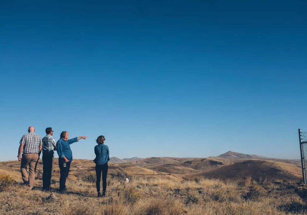 Image of four people overlooking a flat landscape scene in Washington State.