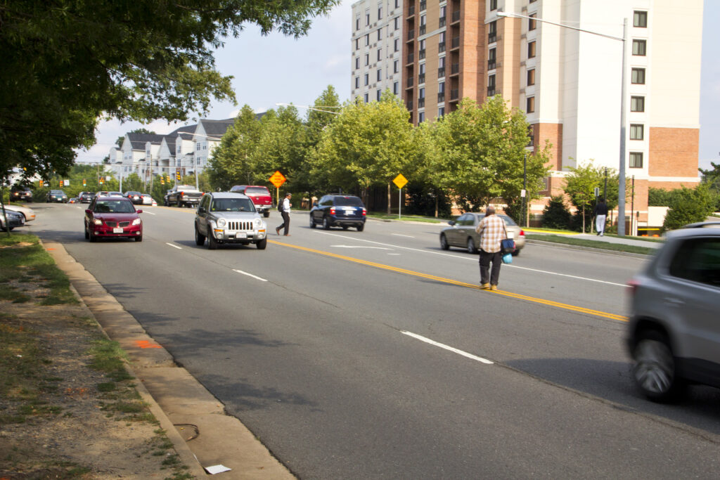 image of people crossing a five-lane street in the DC metro area where there are no sidewalks and crosswalks far apart near a metro station